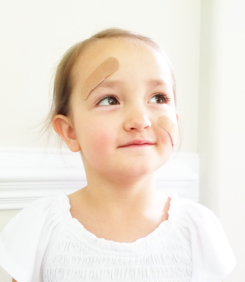 Young girl wearing a band-aid. The band-aid was first created in 1920