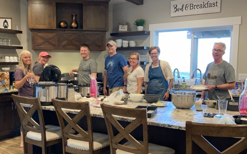 A photo of Camille's family in the kitchen having family dinner.