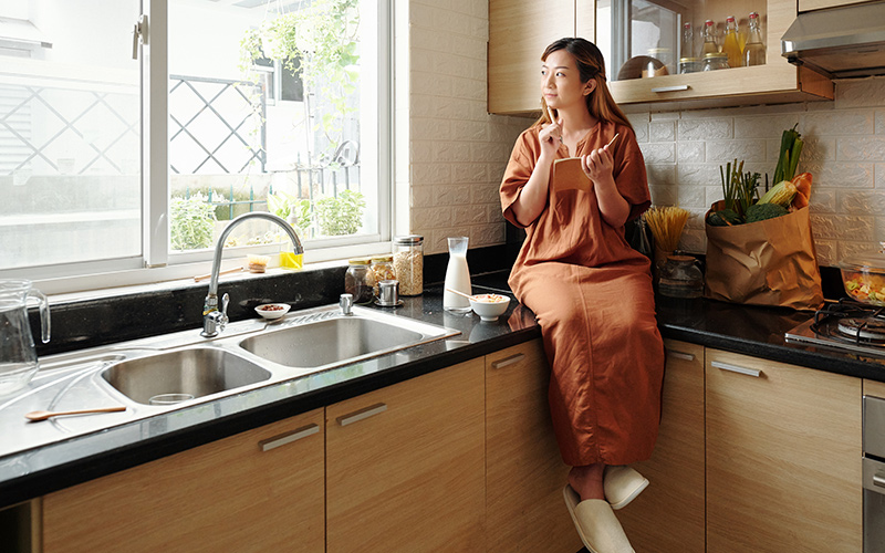Woman in kitchen thinks about what she is grateful for.