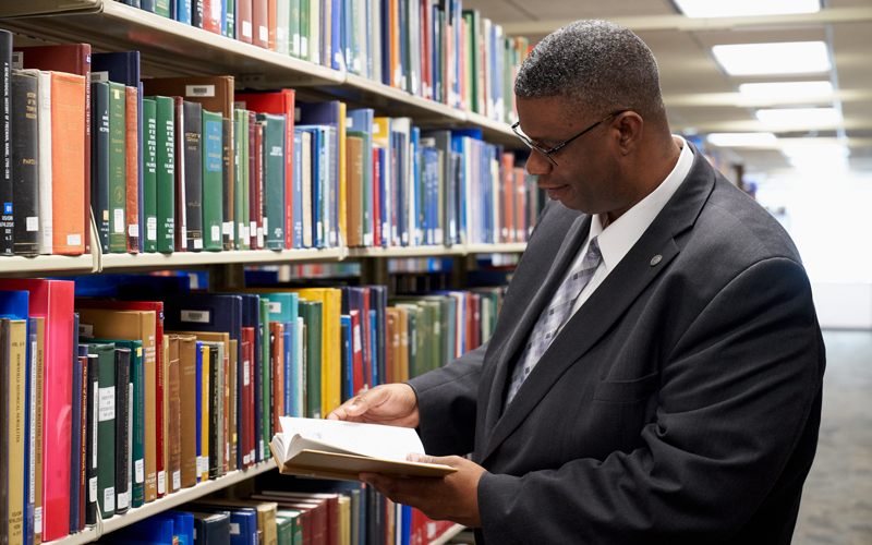 Man reads book at Family History Library
