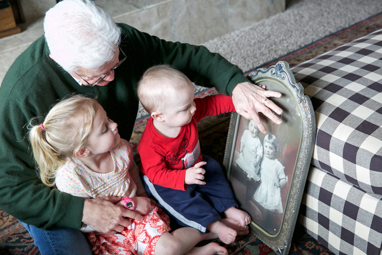 A grandfather shows images to his grandkids.
