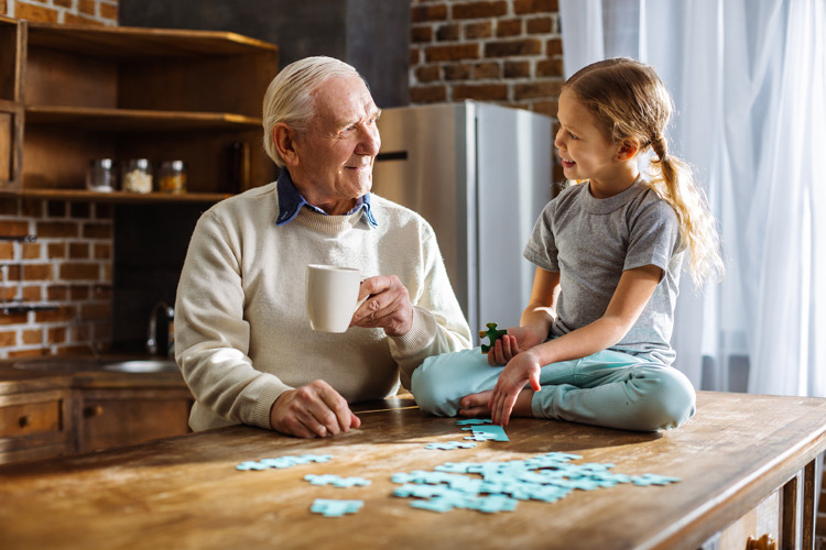 a grandpa and granddaughter do a puzzle together.