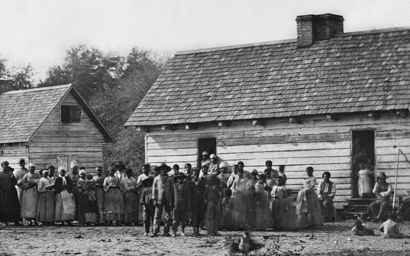 enslaved persons in front of their homes.