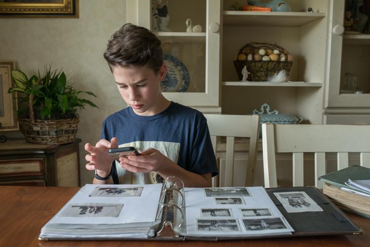 a boy takes photos of his family photos.