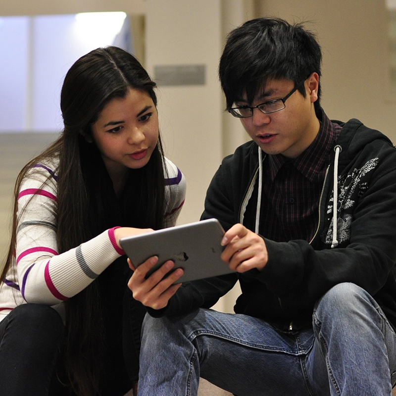 a girl teaches a boy on his ipad.